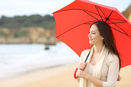 longing: Portrait of a longing woman thinking and looking at horizon under a red umbrella on the beach with the sea in the background