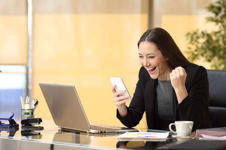Opgewonden zakenvrouw winnen na het bereiken het lezen van een slimme telefoon zitten in een Desktop op kantoor