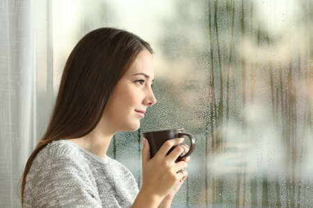 Side view portrait of a pensive woman looking away through a wet window in a rainy day at home