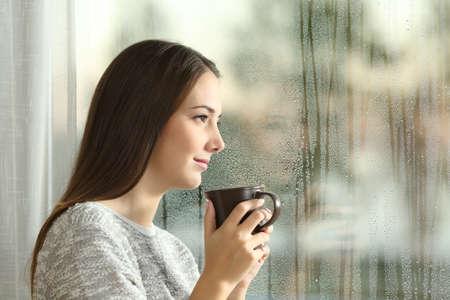 Zijaanzicht portret van een peinzende vrouw weg te kijken door middel van een natte venster in een regenachtige dag thuis