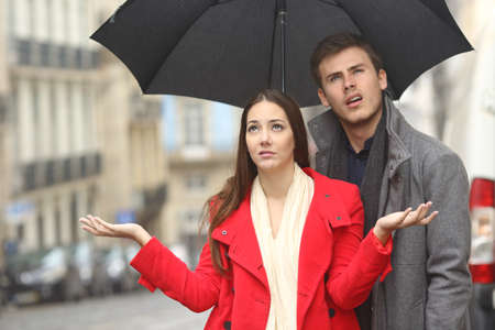 Portret van een weerzinwekkend paar geërgerd in een regenachtige dag onder de regen en een paraplu in de winter Stockfoto
