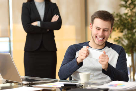 slacker: Lazy employee playing games with his smartphone sitting in a desktop while his angry boss is watching at office Stock Photo