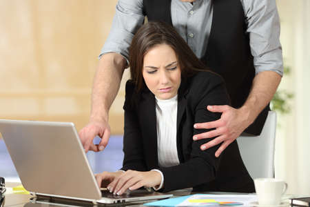 relaciones sexuales: El acoso con un jefe de tocar el brazo a su secretaria que está sentado en su lugar de trabajo en la oficina