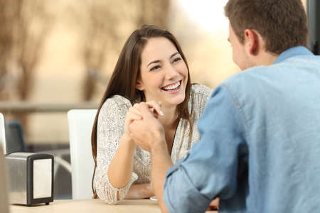 customer facing: Happy couple dating and flirting and holding hands together in a coffee shop with a sunset light outdoor in the background