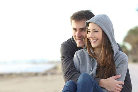 mujer mirando el horizonte: Casual feliz pareja adolescente citas y abrazos que se sienta al aire libre y mirando el horizonte en la playa