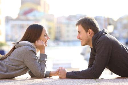 Vista laterale di un paio di adolescenti che risalgono e flirtare che si innamorano guardandosi a vicenda sdraiato sul pavimento in un porto sulle vacanze Archivio Fotografico - 65460868