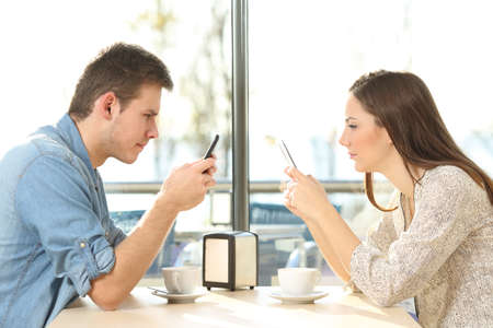 antisocial: Side view of a couple on line everyone obsessed with their own smart phones in a coffee shop Stock Photo
