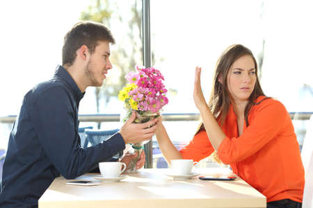 Man asking for forgiveness offering a bunch of flowers to his girlfriend in a coffee shop with an exterior background. Couple problems concept Foto de archivo