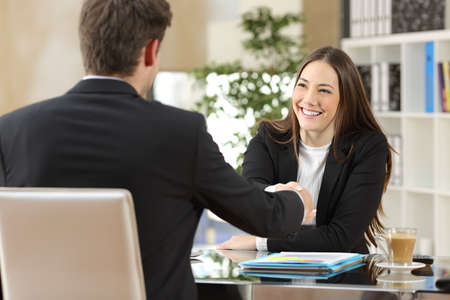 woman boss: Businesspeople handshaking after negotiation or interview at office