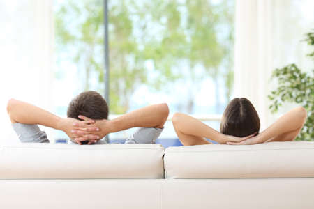 Rear view of a couple relaxing on a sofa at home and looking outside a green background through the window of the living room Reklamní fotografie - 65460874