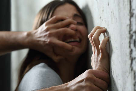 human gender: Sexual abuse with a man attacking to a scared woman in a dark place Stock Photo