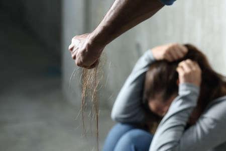 Violência doméstica com um homem ferido por uma mulher aterrorizada puxando o cabelo e segurando-o no punho em um lugar escuro
