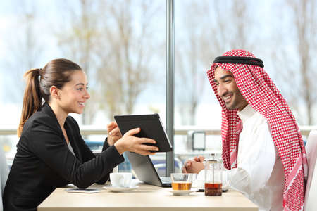 Businesswoman or saleswoman working with an arab man showing products in a tablet in a coffee shop Stock Photo