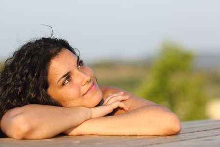 soñando: chica cándida soñando y pensando apoyado en una mesa al aire libre Foto de archivo