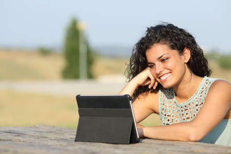 Happy girl watching videos in a tablet in a park outdoors Stock Photo