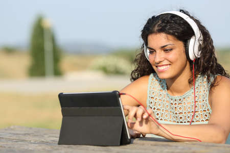 using tablet: Girl learning with a tablet and headphones in a park