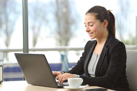 Empresaria feliz escribiendo que trabaja en un ordenador portátil en un restaurante