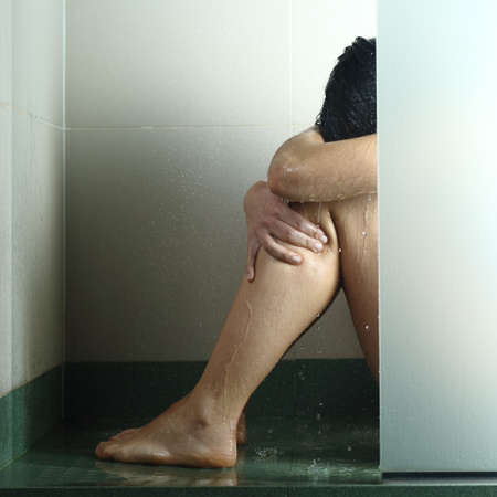 agression: Sad woman after abuse crying under the water in the shower