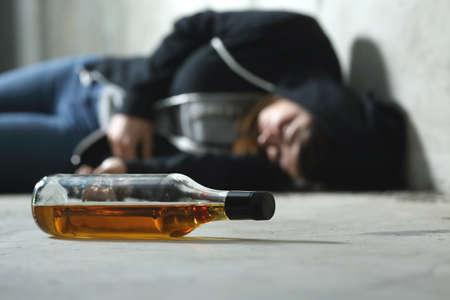 暗い、悲しい場所に床とフォア グラウンドでアルコール ボトルの代で酔って 写真素材