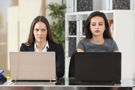 Vooraanzicht van twee boze ondernemers kijken elkaar met haat werken met laptops op het kantoor van Stockfoto