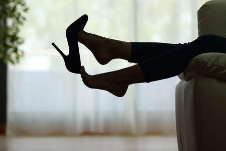 Achterlicht silhouet van een vrouw die met voeten rust, met een schoen op een bank thuis met een raam op de achtergrond Stockfoto