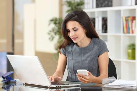 Uitvoerende werken op lijn met een laptop en telefoon in een Desktop op kantoor