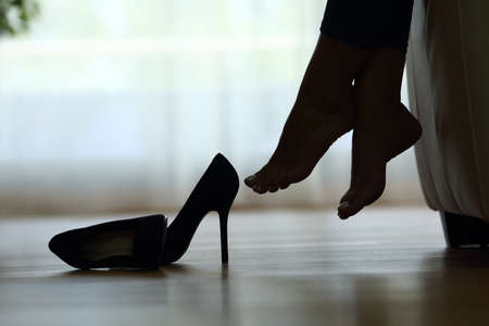 Gegenlicht Silhouette einer Frau Füße ruhen zu Hause mit Schuhen auf dem Boden Standard-Bild - 64920421