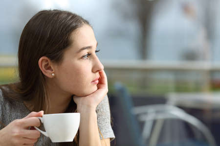 Pensive woman holding a coffee cup looking away in a restaurant terrace in a rainy day Stock Photo