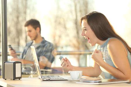 백그라운드에서 큰 창문이있는 식당에서 랩톱 컴퓨터를 사용하여 온라인 컨설팅 수상 경력에 빛나는 승자의 측면보기 초상화 스톡 콘텐츠