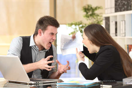 Two angry businesspeople arguing furious showing a negative growth graph at office