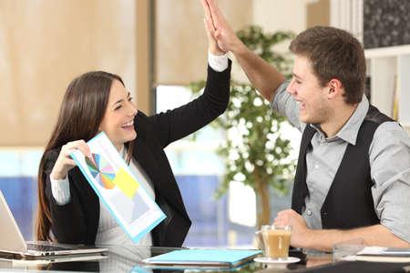 Succesvolle collega met een groei grafiek vieren goede resultaten en het geven van hoge vijf in een kantoor interieur
