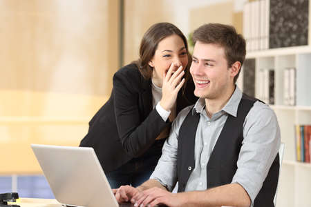 spread the word: Gossip businesswoman telling secrets to the ear of a businessman sitting on a desktop at office