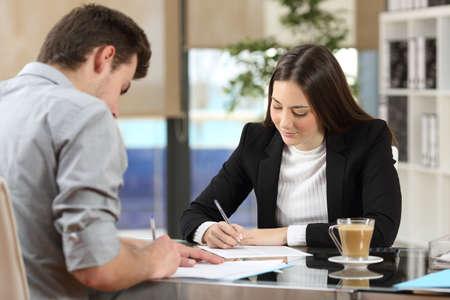 Businesspeople firma contratti insieme dopo un affare in un desktop in ufficio Archivio Fotografico - 64936496