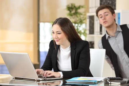 Zakenman spioneren zijn collega die aan het werk op haar bureaublad werkt