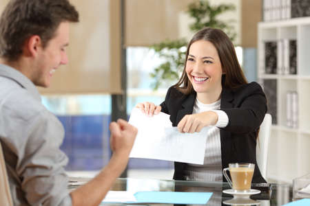 Businesswoman breaking contract with a happy client at office