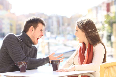 Angry casual couple arguing and shouting each other in a bar terrace outdoors with a vacational port background. Disagreement concept Stock Photo