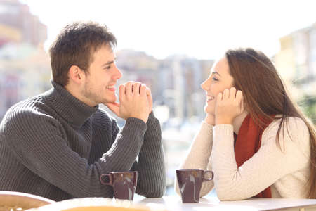 Zijaanzicht van een gelukkige paar dat in liefde kijkt en flirtert in een barterras met een urbanisatiehaven op de achtergrond Stockfoto - 64936523