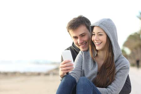 Portrait d'un couple d'adolescents qui regardent le contenu des médias dans un téléphone intelligent en plein air dans la plage Banque d'images - 64936818