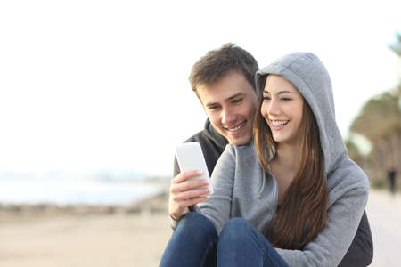 Portrait of couple of teenagers watching media content in a smart phone outdoors in the beach Stok Fotoğraf - 64936818