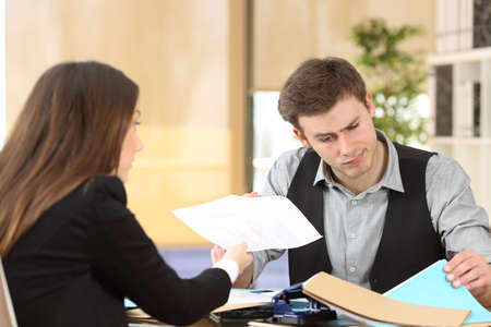 disorganized: Incompetent businessman with disordered desktop attending an upset client giving her a dirty report at office Stock Photo