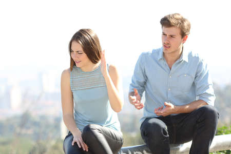 Angry couple arguing outdoors in a park with city in the background Stock Photo