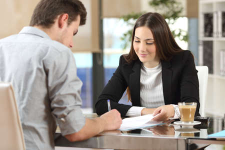 Client signing a document in an office with a businesswoman looking the contract 스톡 콘텐츠