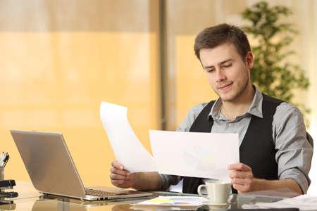 hombre de negocios atenta que trabaja la comparación de documentos en papel que se sientan en un escritorio en la oficina Foto de archivo