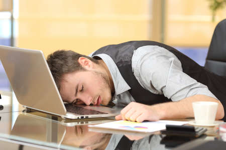 Tired overworked businessman sleeping over a laptop in a desk at job in his office