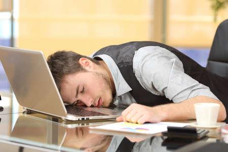 Zmęczony przepracowany biznesmen spanie na laptopie w biurku w pracy w swoim biurze