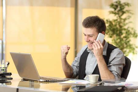 Opgewonden zakenman praten op de mobiele telefoon tijdens het kijken naar zakelijke inhoud in een laptop