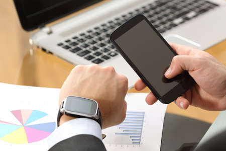 synchronizing: Businessman hands synchronizing on line a smart watch and phone sitting in a desktop at office with a computer in the background Stock Photo