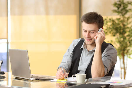 postit note: Entrepreneur working on the phone and writing notes sitting in a desk at office Stock Photo