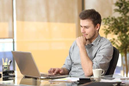 気配りのある起業家の執務室の机に座ってラップトップをブラウジング ラインで作業