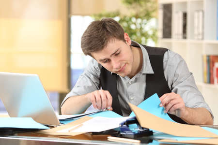 slacker: Incompetent messy businessman with disorganized desk searching lost documents at office Stock Photo